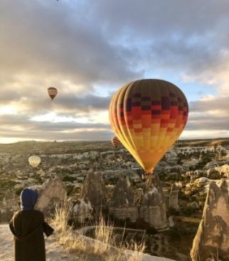 На фотографии Платон Татаринов ( 6 лет, Москва), на фоне восходящего солнца и парящих воздушных шаров в национальном парке Гареме, Каппадокия (Турция)