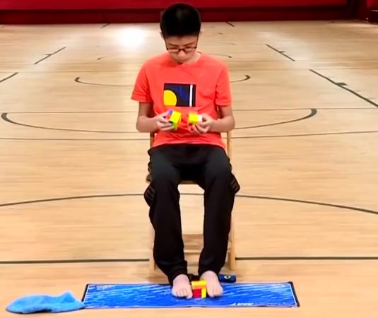 Подросток установил мировой рекорд, собрав 3 кубика Рубика одновременно, причём один из них ногами